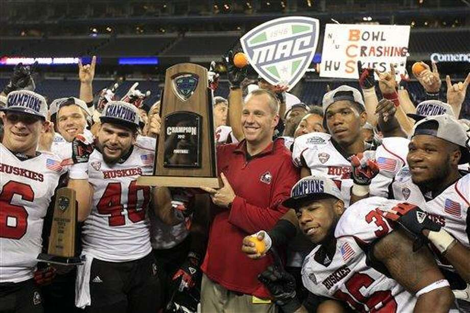 Northern Illinois head coach Dave Doeren, center, holds the Mid-American Conference championship trophy after defeating Kent State 44-37 in the second overtime in an NCAA college football game at Ford Field, Friday, Nov. 30, 2012, in Detroit. (AP Photo/Carlos Osorio) Photo: ASSOCIATED PRESS / AP2012