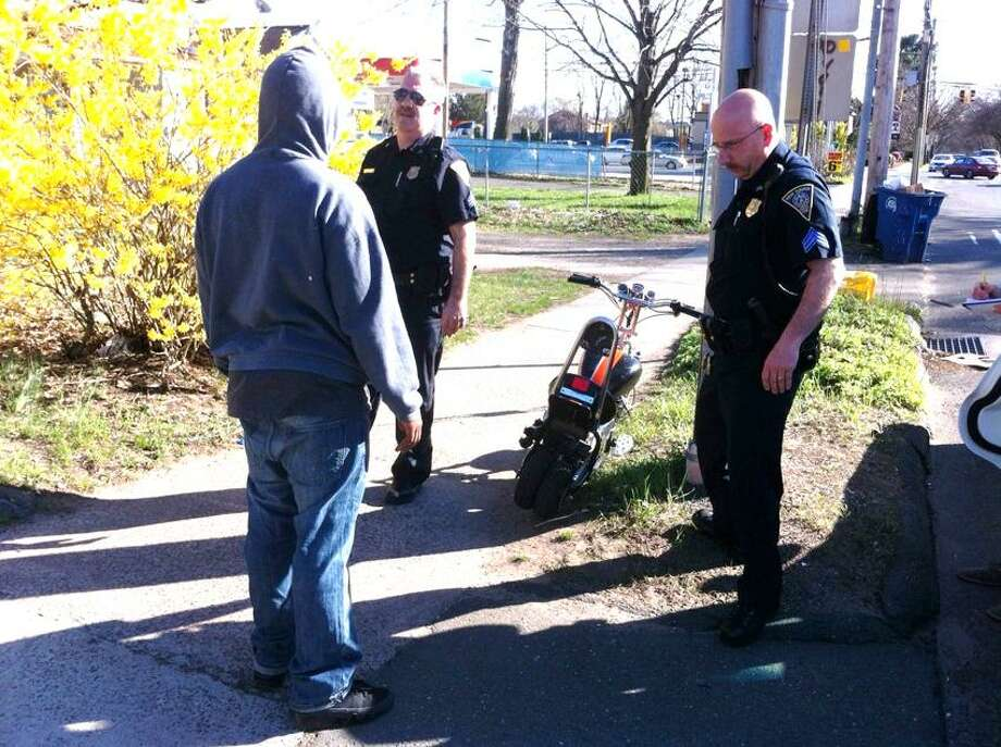 New Haven police Sgt. Vin Anastasio, left, and Sgt. Tony Zona talk with a young man seen wheeling a minibike down Roosevelt Street in New Haven.