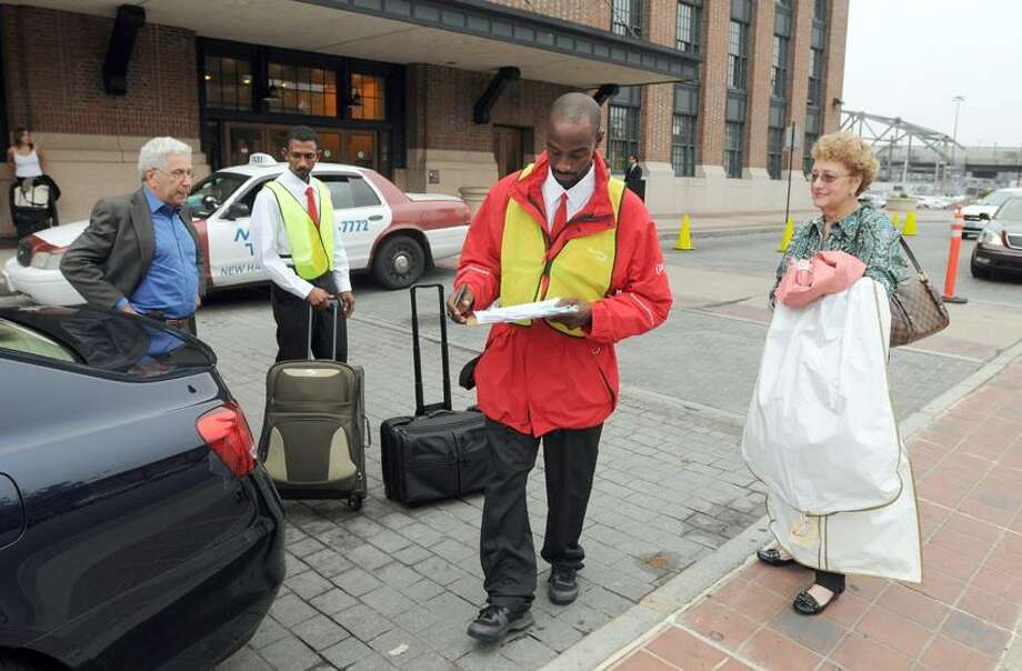 "Left to right: Carl Donatello of Waterford, left,  uses the new Park New Haven valet services at Union Station in New Haven as valet  Musaab Mohammed  and valet captain Lue (CQ) Hemingway work together to help him and his wife Linda Donatello as they rush to catch a train Thursday, October 4, 2012.  Park New Haven has added  a new valet parking service to customers at Union Station. Among the benefits of the new valet parking service will be the ability for customers who are traveling on Amtrak and Metro-North trains into New Haven to send a text message ahead of their arrival to the new ""Rapid Return"" line and have their vehicle waiting for them when they arrive. The valet parking program was a joint effort between Park New Haven and the Connecticut Department of Transportation (CTDOT). The CTDOT owns Union Station, while Park New Haven maintains and operates the property. Photo by Peter Hvizdak / New Haven Register Photo: New Haven Register / ©Peter Hvizdak /  New Haven Register"