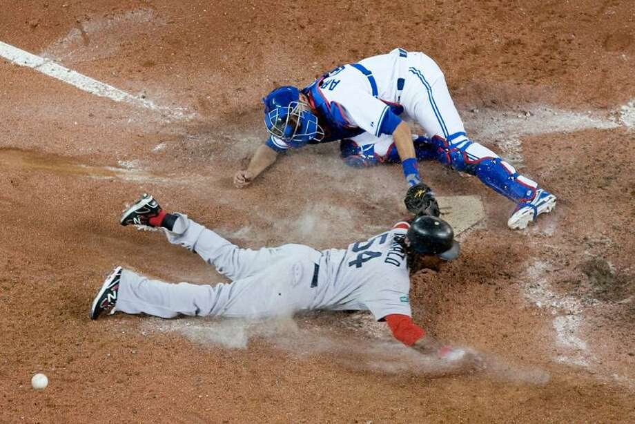 Boston Red Sox's Darnell McDonald slides into home plate to score against Toronto Blue Jays catcher J.P Arencibia during the ninth inning of a baseball game in Toronto on Monday, April 9, 2012. Boston won 4-2. (AP Photo/The Canadian Press, Chris Young) Photo: AP / The Canadian Press
