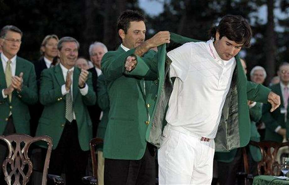 Charl Schwartzel, left, of South Africa, helps Bubba Watson put on the winner's green jacket after winning the Masters golf tournament on the 10th hole after a sudden death playoff Sunday, April 8, 2012, in Augusta, Ga. (AP Photo/Darron Cummings) Photo: ASSOCIATED PRESS / AP2012