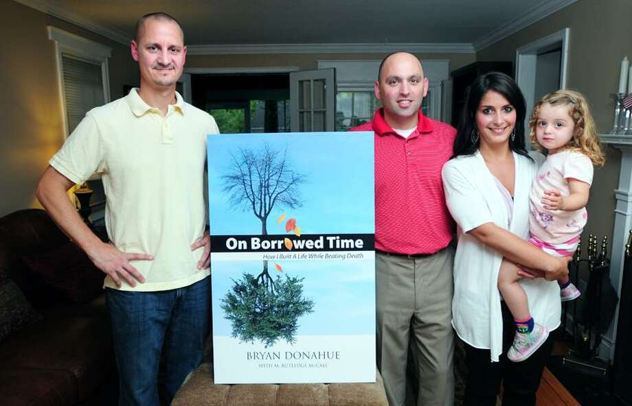 Arnold Gold/Register photo: Bryan Donohue, center, here with his wife, Lia, and daughter, Lily J., wrote a book about his liver transplant experience, and says he owes his life to his donor brother-in-law Jeff Agli, left.