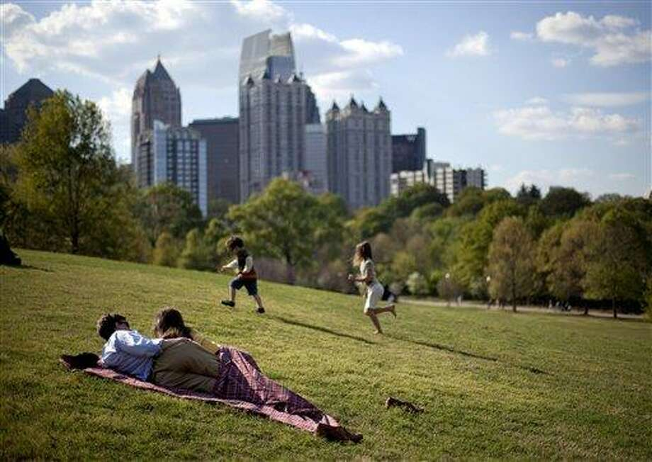A couple enjoy a sunny afternoon March 25 against the backdrop of the Midtown skyline from Piedmont Park in Atlanta. The lower 48 states were 8.6 degrees above normal for March and 6 degrees higher than average for the first three months of the year, according to calculations by the National Oceanic and Atmospheric Administration, with both March and the first three months of the year far exceeding the country's old records. Associated Press Photo: AP / AP