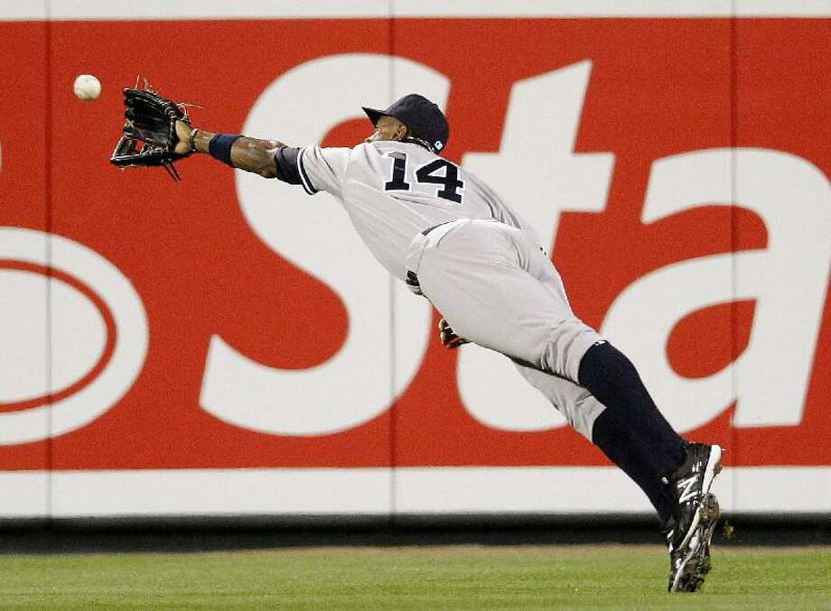 ASSOCIATED PRESS New York Yankees center fielder Curtis Granderson dives but can't catch a fly ball hit by Baltimore's Robert Andino in the third inning of Monday's game in Baltimore. The Yankees took the game 6-2 for their first victory of the season.