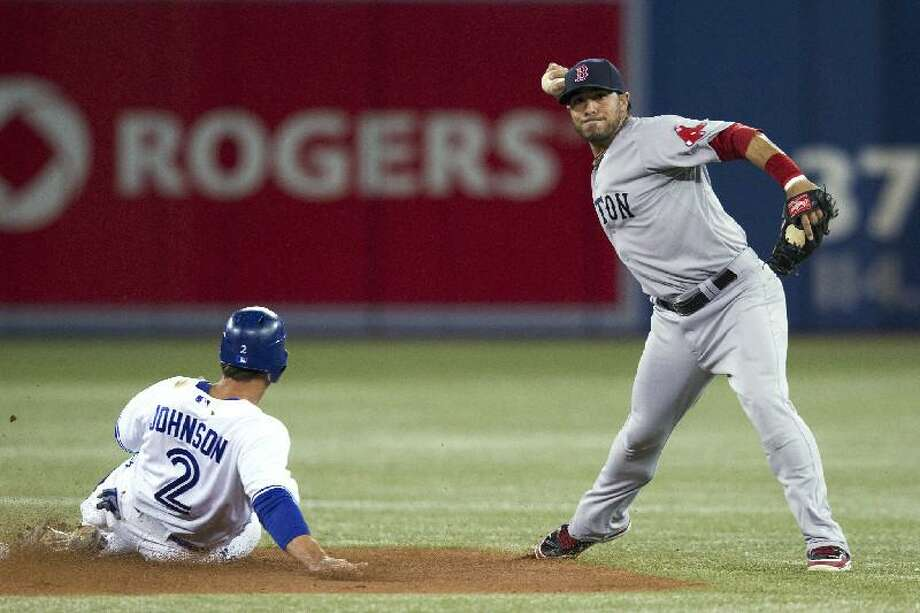 ASSOCIATED PRESS Boston Red Sox shortstop Mike Aviles throws to first to complete a double play after forcing out Toronto's Kelly Johnson during Monday night's game in Toronto. The Red Sox rallied for a 4-2 win, their first of the season.