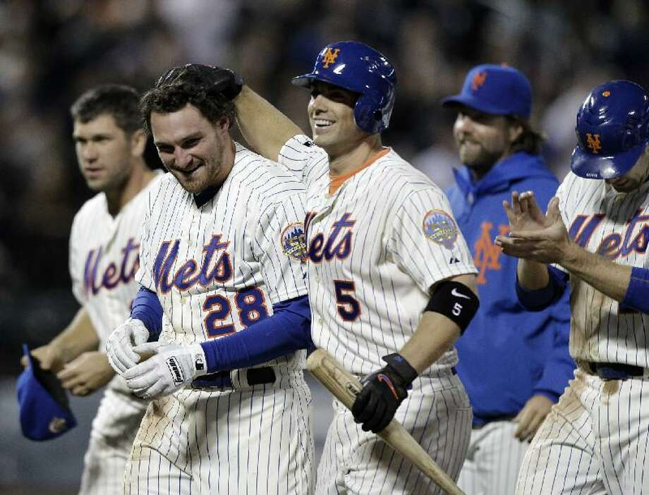 ASSOCIATED PRESS New York Mets catcher Josh Thole, left rear, and David Wright (5) celebrate with Daniel Murphy after the Mets' 4-3 victory over the Washington Nationals on Monday night in New York. Murphy hit a single in the ninth that scored Mike Baxter to give the Mets their fourth straight win. Mets pitcher R.A.Dickey is second from right.