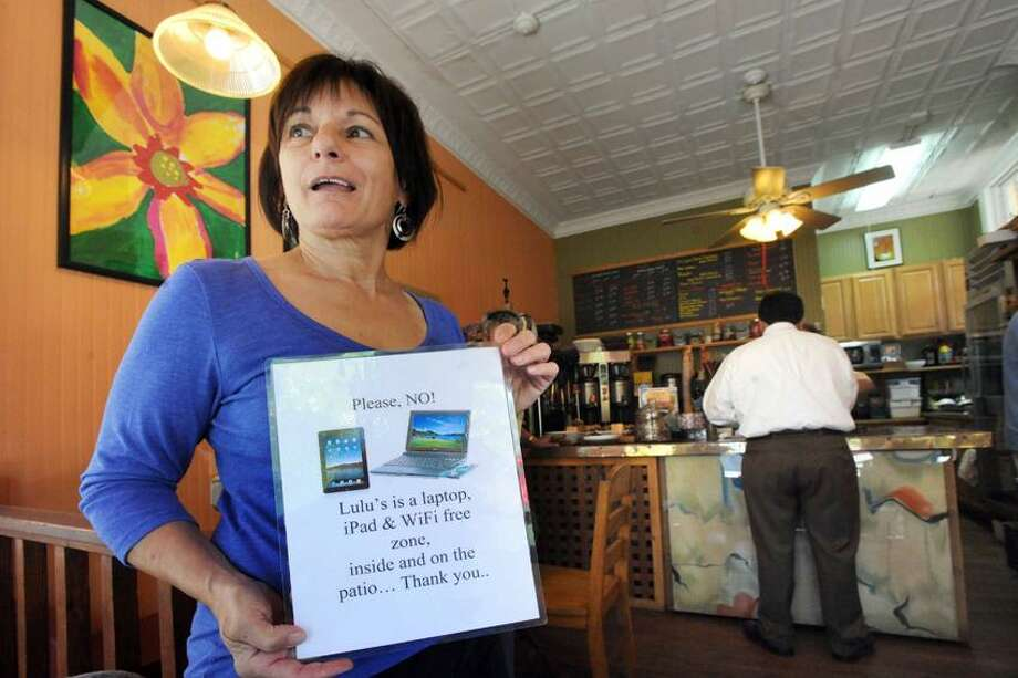 Lulu de Carrone, owner of Lulu's Coffeehouse at 49 Cottage St in New Haven holds a sign thats posted around the store telling patrons that laptop and cellphone use aren't allowed. 07.25.12 vm Williams