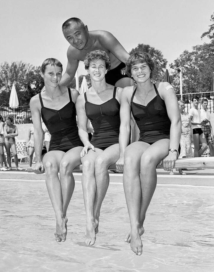Two-time Olympic Champion Sammy Lee of Santa Ana, Calif., stands behind three members of the U. S. Womens Olympic Swimming and Diving Team, left to right are: Paula Myers Pope, Glendora, Calif., Mrs. Juno Irwin; Mesa, Ariz., and Patsy Willard, Glendale, Calif., at Renaissance Country Club, Roslyn Heights, Aug. 7, 1960, New York. Sammy, who is coaching these gals, is hoping for medals at the Olympics. Photo: AP / 1960 AP