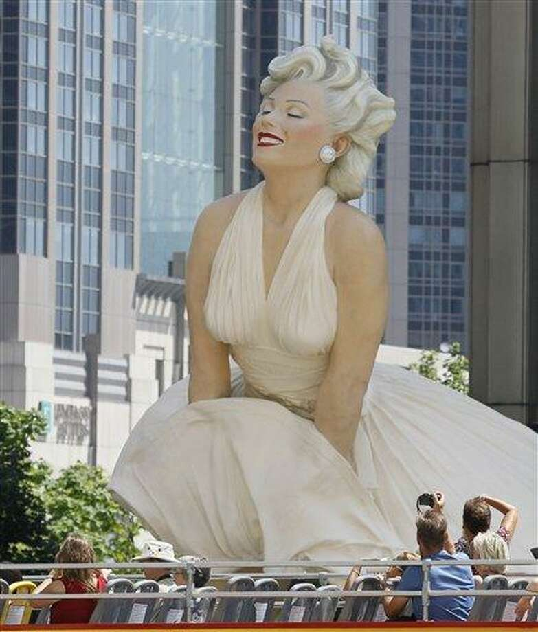 FILE - In this July 15, 2011 file photo, tourists on a double decker bus photograph Seward Johnson's 26-foot-tall sculpture of Marilyn Monroe, in her most famous wind-blown pose, on Michigan Avenue, in Chicago. (AP Photo) Photo: ASSOCIATED PRESS / AP2011