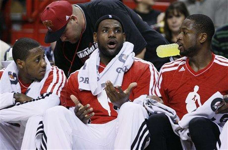 Miami Heat forward LeBron James, center, reacts to a play as he watches from the bench with guards Mario Chalmers, left, and Dwyane Wade during the first half of an NBA basketball game against the Brooklyn Nets, Saturday, Dec. 1, 2012 in Miami. (AP Photo/Wilfredo Lee) Photo: AP / AP