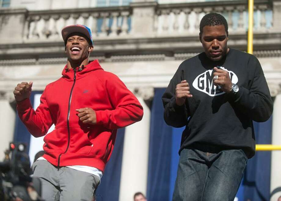 New York Giant's Victor Cruz, left, is joined by former Giants plyer Michael Strahan as they salsa dance during a ceremony for the NFL football Super Bowl XLVI champions at City Hall in New York, Tuesday, Feb. 7, 2012.  (AP Photo/Craig Warga, Pool) Photo: ASSOCIATED PRESS / AP2012