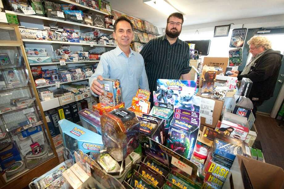 Dave Yaccarino, owner and store employee Ben Gritz pose in the sales area of DJ's Comics at 1 Lincold St North Haven as store patron Don Kahen looks through some store items November 30, 2012. vm Williams