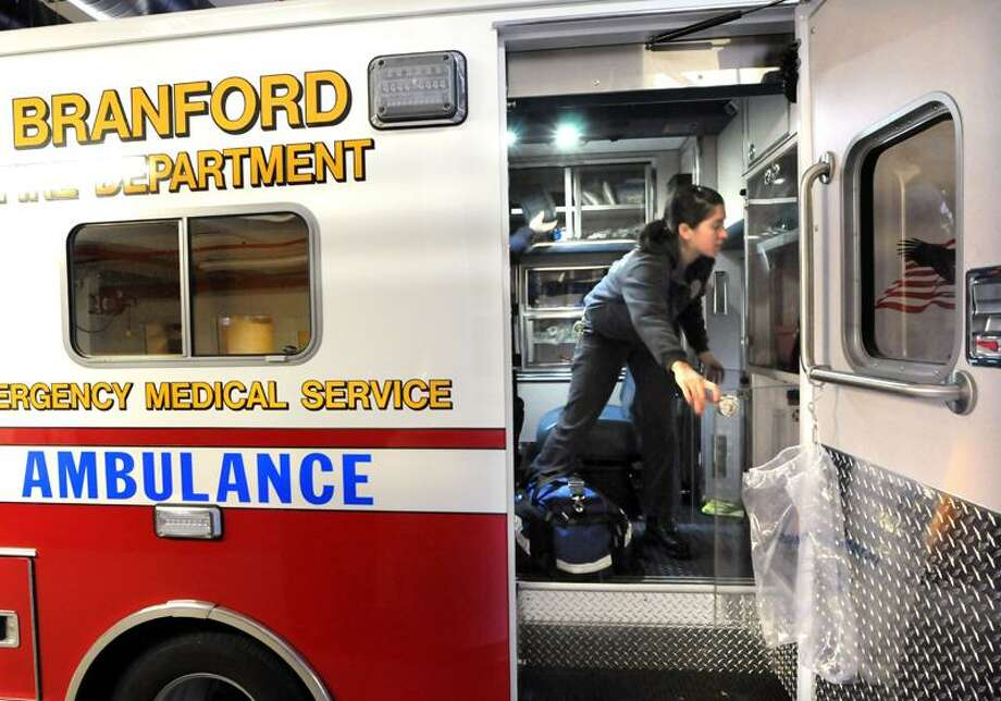 At Branford fire department headquarters, Branford Firefighters/Paramedics Amanda Mark and Jeff O'Connor work through a truck check on the department's ambulance. The check makes sure that all supplies are current and on board.  Mara Lavitt/New Haven Register12/1/12