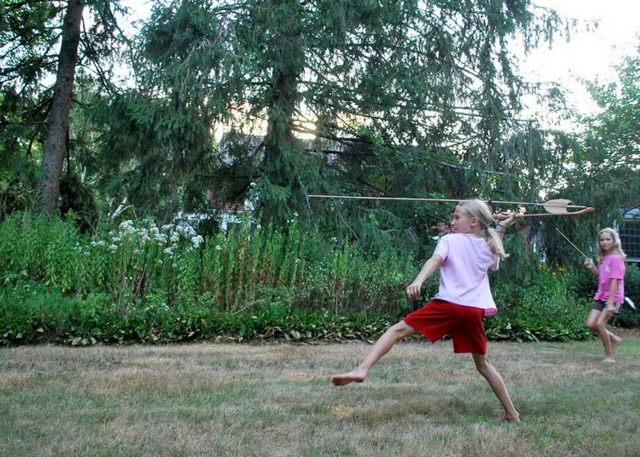 Laurie Rankin photo: Gigi Rankin demonstrates how to toss a spear with an atlatl. Try it at Hammonasset Jamboree this weekend in Madison.