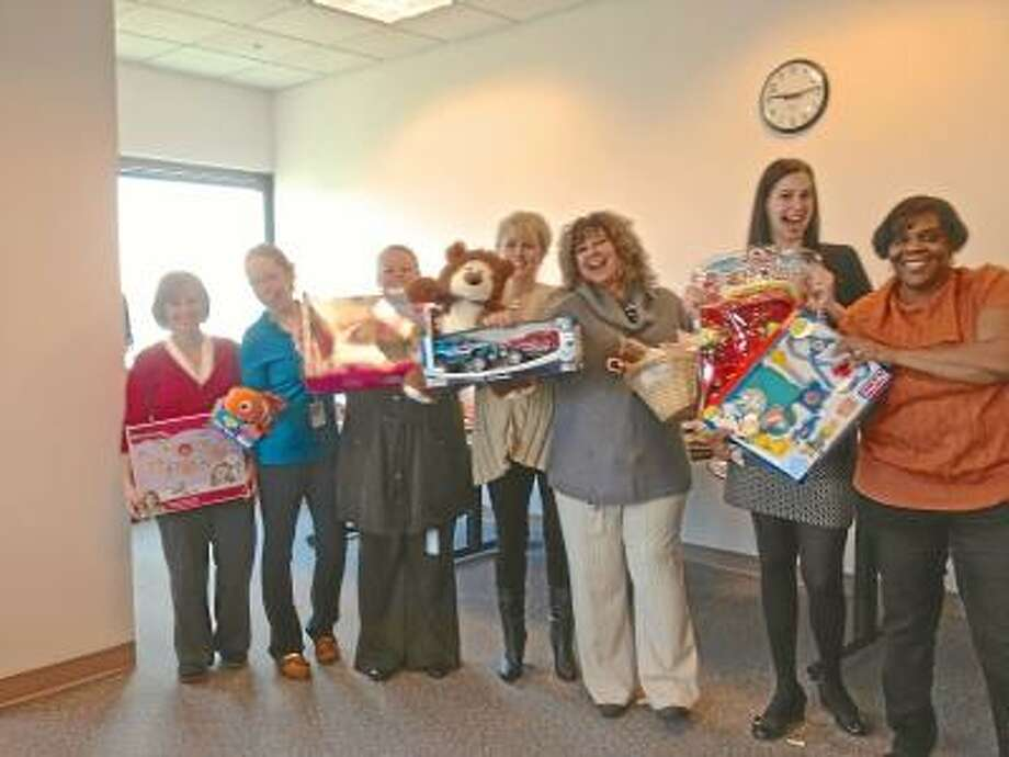Lauren Sievert/The Middletown Press Christmas Workshop Committee members stand with some of the toys that will be donated to children in need for Christmas.