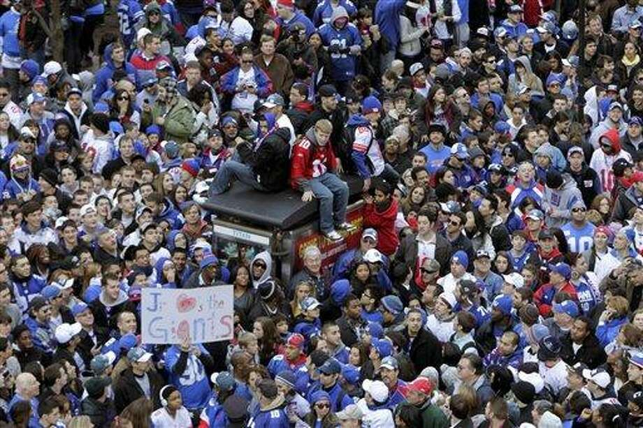 Fans line the streets in lower Manhattan waiting for the start of the New York Giants Super Bowl parade in New York Tuesday. Associated Press Photo: ASSOCIATED PRESS / AP2012