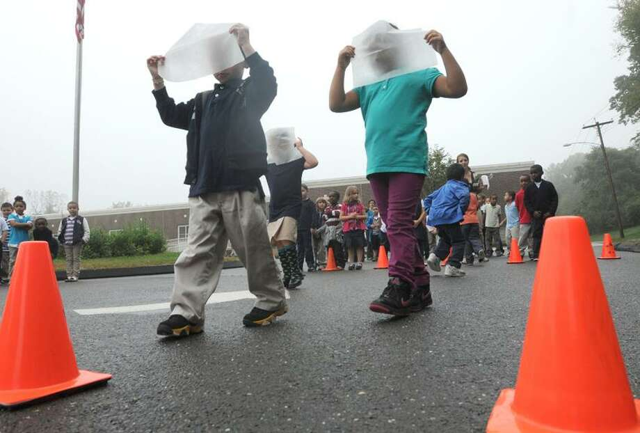 First-graders hold plastic sheeting over their faces to simulate foggy walking conditions during the Safe Kids Greater Naugatuck Valley and Griffin Hospital sponsored community outreach where nurses join students at the K-6 John C. Mead Elementary School in Ansonia to raise awareness about pedestrian safety on International Walk to School Day.   Photo by Peter Hvizdak / New Haven Register Photo: New Haven Register / ©Peter Hvizdak /  New Haven Register