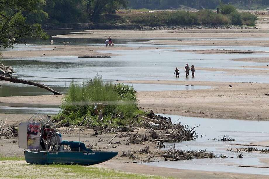 This photo from July 31 shows a beached air boat as bathers walk in the nearly dry Platte River near Yutan, Neb., Tuesday. The latest U.S. Drought Monitor survey shows an increase in extreme drought conditions in four Plains states, but a slight decrease in the overall area of the lower 48 states experiencing some form of drought. (AP Photo/Nati Harnik) Photo: ASSOCIATED PRESS / 02012