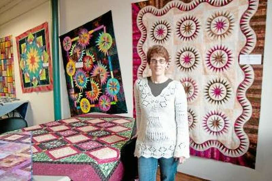 Max Lauf/Register Citizen Jackie Kunkel, of Canton Village Quilt Works, in front of her quilts at the Whiting Mills Open Studio event in Winsted. / Max WIlliam Lauf