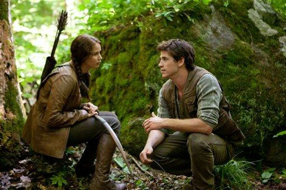 """In this image released by Lionsgate, Jennifer Lawrence portrays Katniss Everdeen, left, and Liam Hemsworth portrays Gale Hawthorne in a scene from """"The Hunger Games."""" (AP Photo/Lionsgate, Murray Close) Photo: AP / AP2011"""