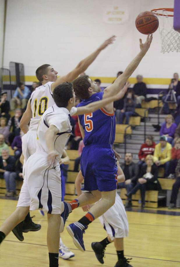 """Dispatch Staff Photo by JOHN HAEGER <a href=""""http://twitter.com/oneidaphoto"""">twitter.com/oneidaphoto</a> Oneida's Kyle Peck (5) drives the lane as Holland Patent's Nick Roberts (10) and Mike Strumpfler (11) defend in the first half of their TVL game in Holland Patent on Tuesday, Feb. 7, 2012. Oneida rallied for a 64-60 win and needs only to win its last game to make the Class A playoffs."""
