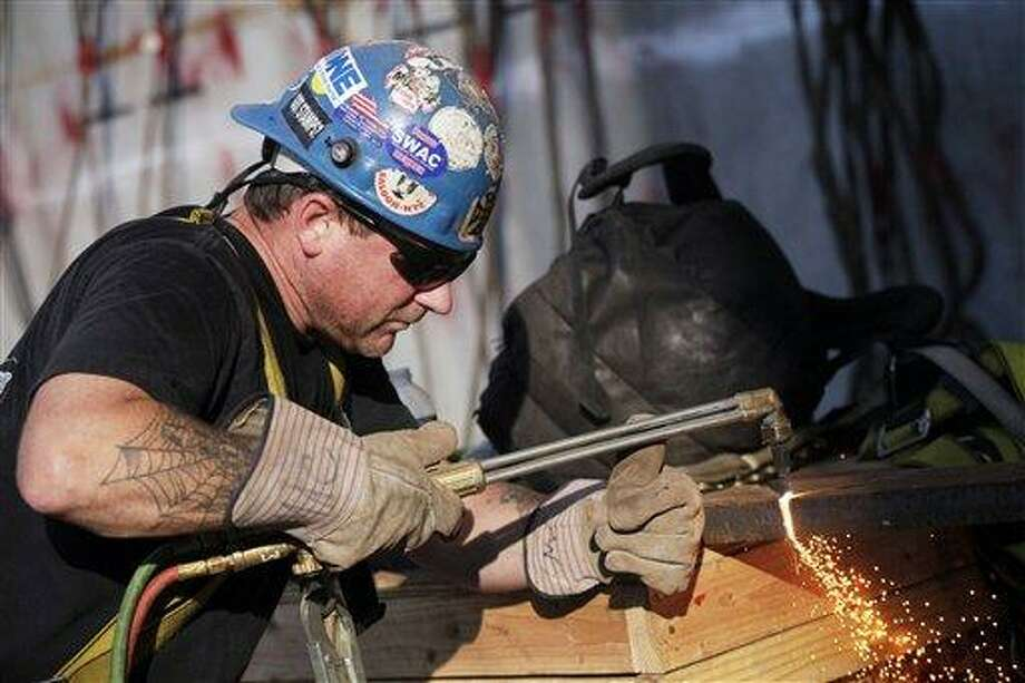 In this Aug. 2, 2012 photo, ironworker Stephen MacGray cuts a steel brace at the World Trade Center construction site, in New York. U.S. employers added 163,000 jobs in July, a hopeful sign after three months of sluggish hiring. The Labor Department said Friday, Aug. 3, 2012, that the unemployment rate rose to 8.3 percent from 8.2 percent in June. July's hiring was the best since February. Still, the economy has added an average of 151,000 jobs a month this year, roughly the same as last year's pace. That's not enough to satisfy the 12.8 million Americans who are unemployed. (AP Photo/Mark Lennihan) Photo: AP / AP