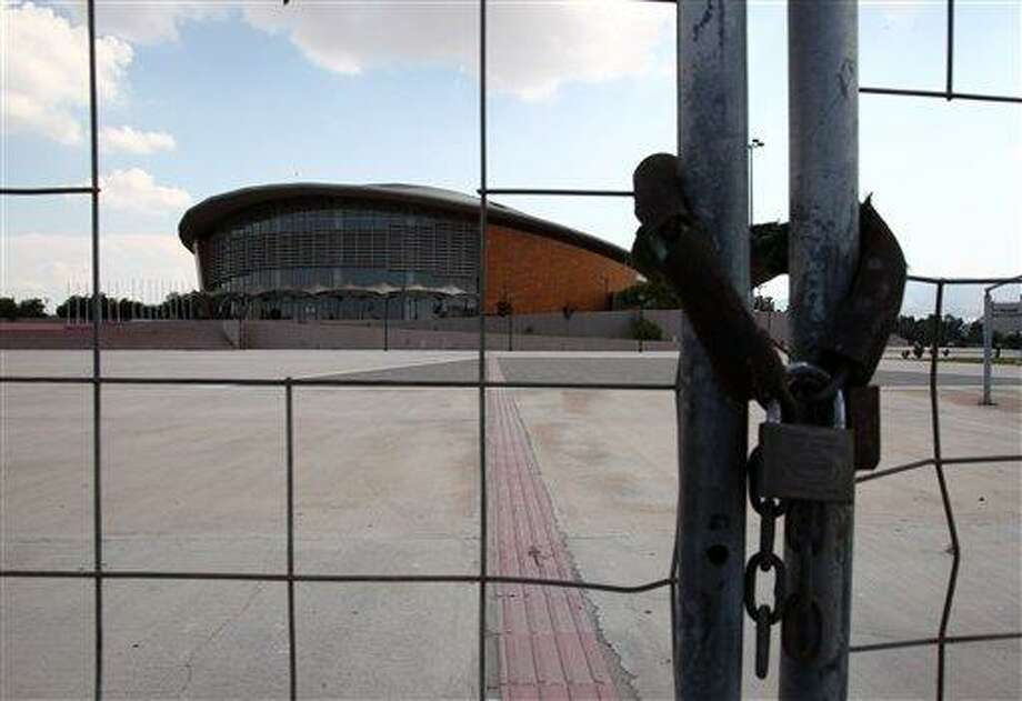 The gate to the Olympic taekwondo and handball arena is locked in southern Athens, Thursday, Aug. 2, 2012. The purpose-built arena has been occasionally used for non-sporting events since the Athens 2004 Olympics. Eight years after the Athens Games, many of the venues remain abandoned or rarely used, focusing public anger on past governments as the country struggles through a fifth year of recession and a debt crisis that has seen a surge in poverty and unemployment. (AP Photo/Thanassis Stavrakis) Photo: AP / AP
