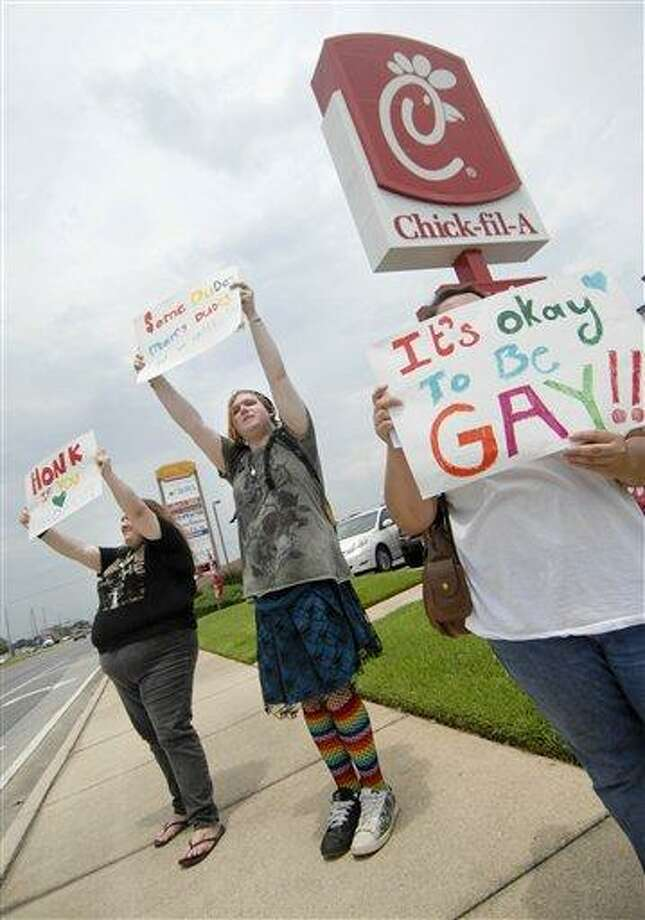 Gay marriage supporters, from left, Emmie Hesley, Cathy Dear and Amy Paffenroth hold signs in front of a Chick-fil-A in Fort Walton Beach, Fla., Thursday  in protest of the chicken eatery's stance on gay marriage. (AP Photo/Northwest Florida Daily News, Nick Tomecek) Photo: AP / Northwest Florida Daily News