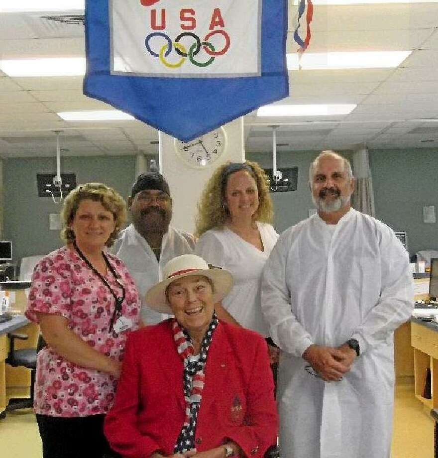 """Darlene """"Poochie"""" Montgomery (front) was selected to be one of the first women to demonstrate judo in the 1980 Olympics, which the United States boycotted. Now, she has a new Olympic team at DaVita Dialysis in Torrington, standing under her Olympic flag signed by the 1980 Olympic judo team. Montgomery is wearing the American Olympic outfit from the 1996 games during which she was the manager of the United States' judo team. Back, from left to right: Jo Madia, Nelson Vega, Tracy Morales-Gabelman and Alex Gubbiotti. (MICHELLE MERLIN/Register Citizen)"""