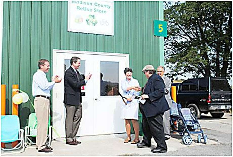 Photo Courtesy REUSE STORE James Goldstein, Chairman of the Madison County Solid Waste and Recycling Committee shakes hands with recycling coordinator Sharon Driscoll following the ribbon cutting on July 19. Also present, from left, were Sen. David Valesky, D-49, Allen Thornton of the Rescue Mission and James A. Zecca, director of the Department of Solid Waste.