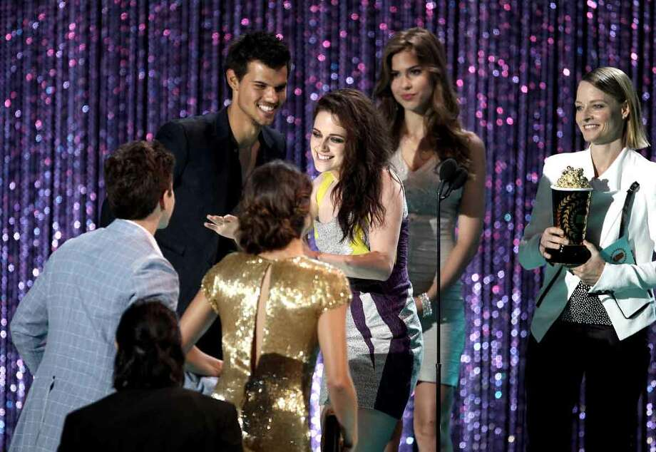 """The cast of """"The Twilight Saga: Breaking Dawn, Part 1"""" is seen on stage as they accept the award for movie of the year from presenter Jodie Foster, right, at the MTV Movie Awards on Sunday, June 3, 2012, in Los Angeles. (Photo by Matt Sayles/Invision/AP) Photo: MATT SAYLES/INVISION/AP / AP2012"""