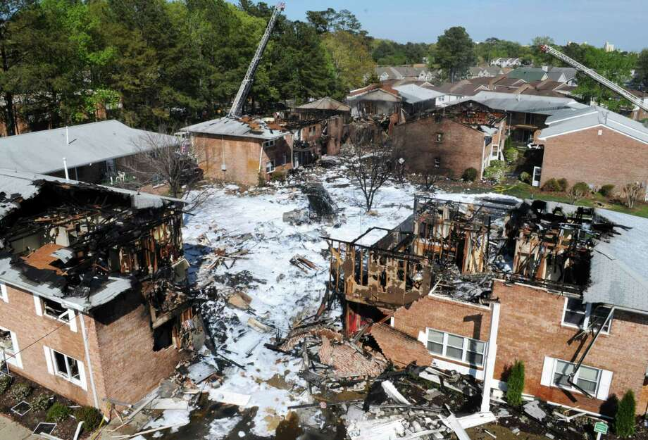 The scene of a jet crash is covered in foam on Friday, April 6, 2012, in Virginia Beach, Va. Two Navy pilots ejected from a fighter jet Friday, sending the unmanned plane careening into a Virginia Beach apartment complex and tearing the roof off at least one building that was engulfed in flames, officials said. Six people, including both pilots, were taken to hospitals, officials said. The Navy said both aviators on board the jet ejected before it crashed around noon and were being taken to hospitals for observation.  (AP Photo/U.S. Navy, Petty Officer 3rd Class Antonio P. Turretto Ramos) Photo: ASSOCIATED PRESS / AP2012