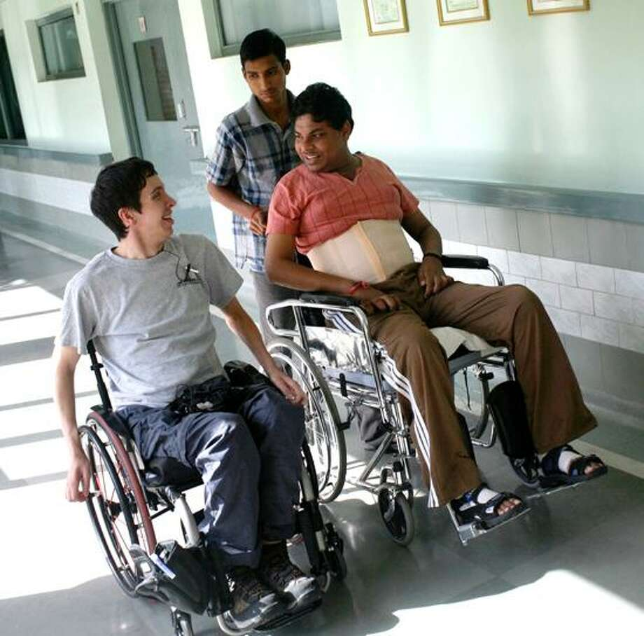 Jon Sigworth visits a patient, Robin, at the Indian Spinal Injuries Center in New Delhi. Photo by Ross Taylor