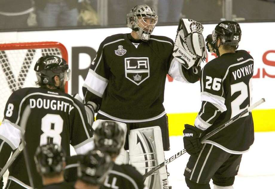 Los Angeles Kings goalie Jonathan Quick, center, is congratulated by teammate Slava Voynov and other teammates after the Kings defeated the New Jersey Devils in Game 3 of the NHL Stanley Cup hockey final in Los Angeles (REUTERS/Alex Gallardo) Photo: REUTERS / X02695