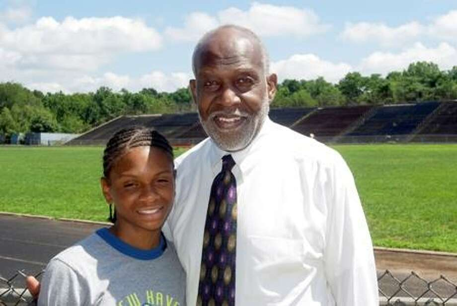 Danae Rivers stands with James Barber, the founder of the New Haven Track Club. Rivers, 14, is a nationally ranked athlete in the 800m and 1500m run.  Eliezer Santiago/ for the Register
