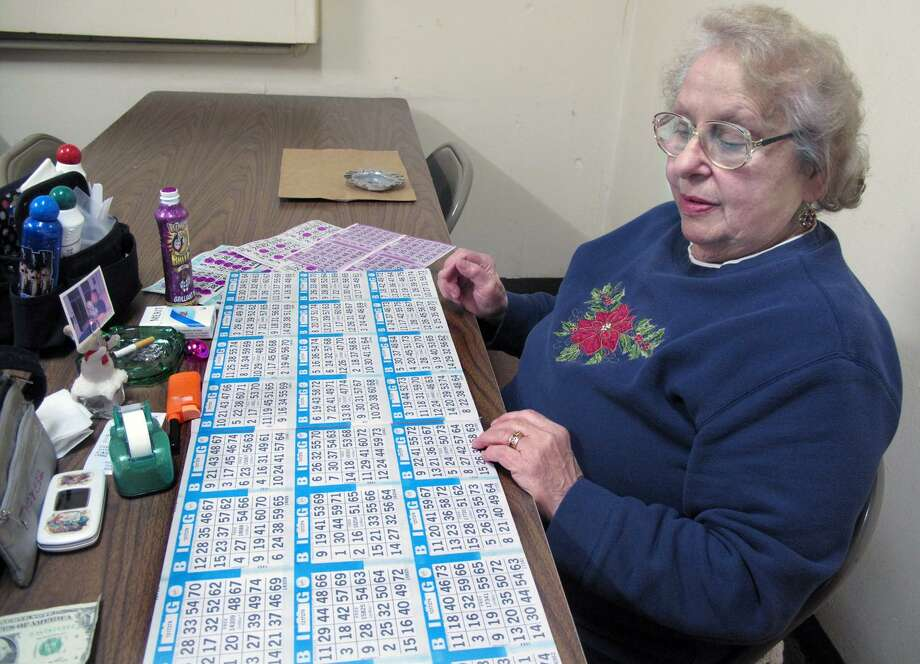 DEBBI MORELLO/Register Citizen Theresa Ross has been coming to St. Maron's Church to play Bingo for nearly 38 years. She is setting up her table at St. Maron's Church on Sunday.