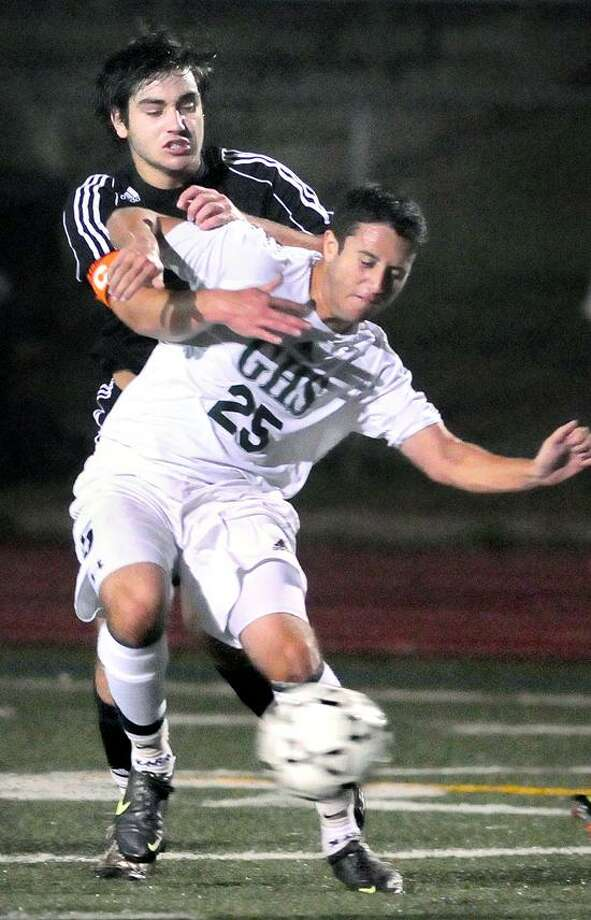 Hand's Tyler Kilkenny, left, battles with Zach Rattet of Guilford for control of the ball in the first half of Hand's 5-1 win Wednesday. Photo by Arnold Gold/New Haven Register