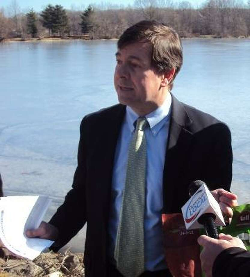 State Sen. Andrew Roraback, R-Goshen, holds up a bag of lawn fertilizer containing phosphorous next to Bantam Lake Monday. Roraback and State Rep. Clark Chapin proposed legislation to limit the use of lawn fertilizer containing phosphorous. (RICKY CAMPBELL/ Register Citizen)