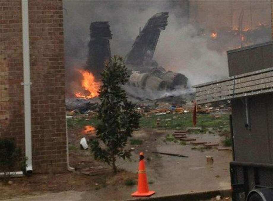 The burning fuselage of an F/A-18 Hornet lies smoldering after crashing into a residential building in Virginia Beach, Va., Friday, April 6, 2012. The Navy did not immediately return telephone messages left by The Associated Press, but media reports indicate the two aviators were able to eject from the jet before it crashed. They were being treated for injuries that were not considered life threatening. (AP Photo) Photo: AP / AP