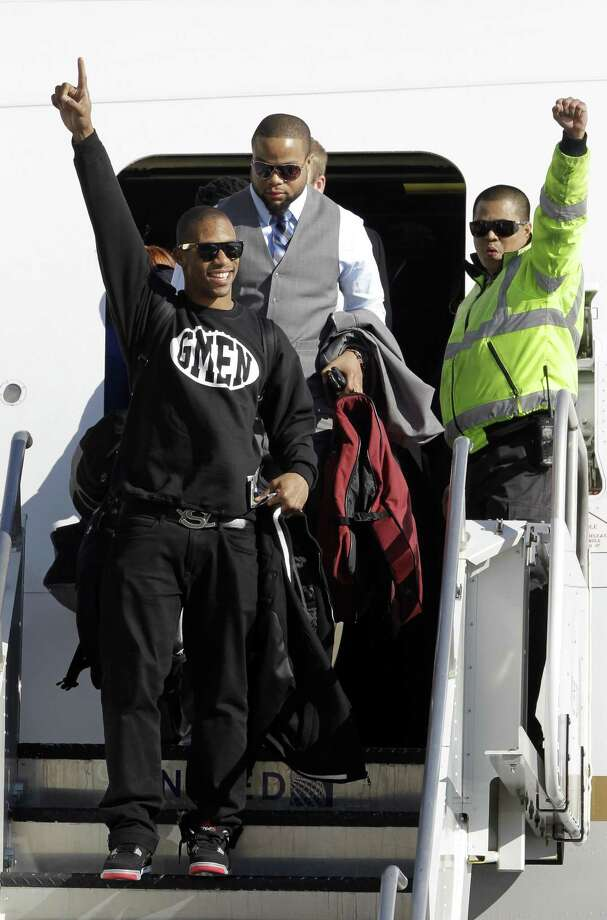 New York Giants wide receiver Victor Cruz, left, arrives with his NFL football team at Newark Liberty International Airport, Monday, Feb. 6, 2012, in Newark, N.J. A day earlier, the Giants beat the New England Patriots in Super Bowl XLVI. (AP Photo/Julio Cortez) Photo: ASSOCIATED PRESS / AP2012