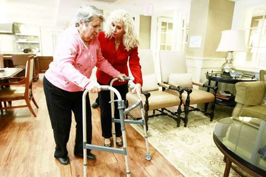 AP Photo/Charles Dharapak Alexis McKenzie, executive director of The Methodist Home of the District of Columbia Forest Side, an Alzheimer's assisted-living facility, walks with resident Catherine Peake, in Washington, Monday, Feb. 6, 2012. Photo: ASSOCIATED PRESS / AP2012