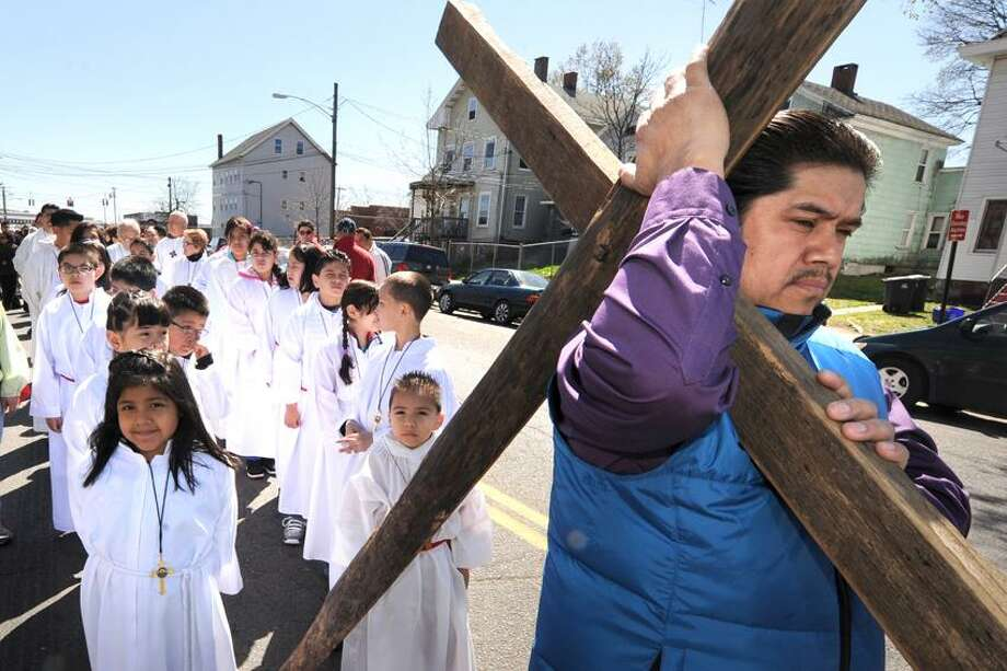"Andres Garcia carries the cross to start the annual ""stations of the cross"" procession of St Rose of Lima Church on Blatchley Ave in Fair Haven Friday, April 6, 2012. vmWilliams"