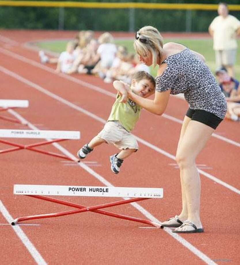 Dispatch Staff Photo by JOHN HAEGER (Twitter.com/OneidaPhoto)Caiden Smithers, 2, gets a little help over the hurdle from his mother Jessica Smithers during a track meet in Canastota on Thursday, Aug. 2, 2012.