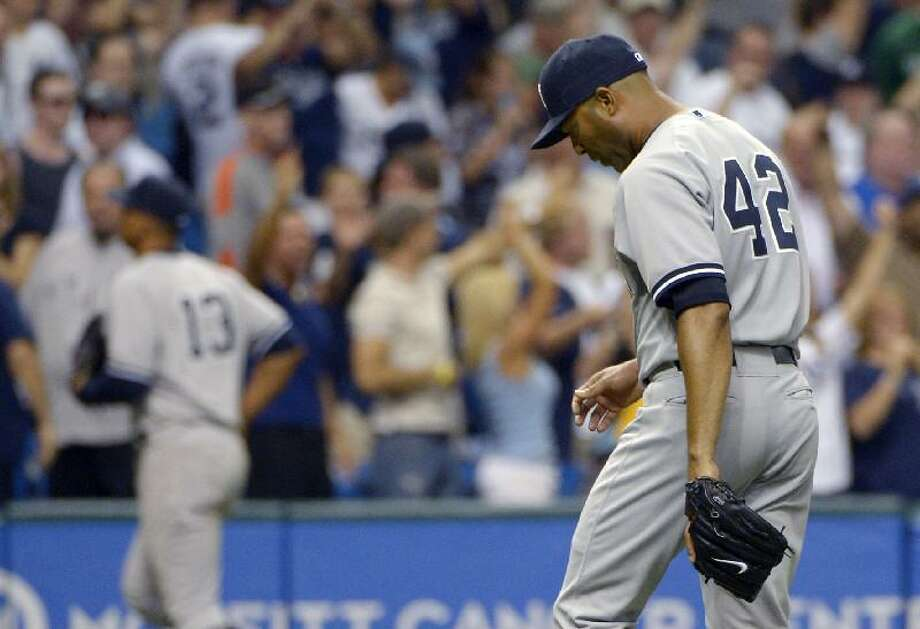 ASSOCIATED PRESS New York Yankees reliever Mariano Rivera, right, walks off the field after giving up a game-winning RBI single to Tampa Bay Rays first baseman Carlos Pena in the bottom of the ninth inning of Friday's game in St. Petersburg, Fla.. The Rays won 7-6.