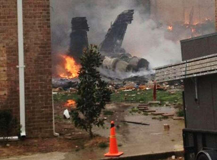 AP Photo/Kandice AngelThe burning fuselage of an F/A-18 Hornet lies smoldering after crashing into a residential building in Virginia Beach, Va., Friday, April 6, 2012. The Navy did not immediately return telephone messages left by The Associated Press, but media reports indicate the two aviators were able to eject from the jet before it crashed. They were being treated for injuries that were not considered life threatening. Photo: ASSOCIATED PRESS / AP2012