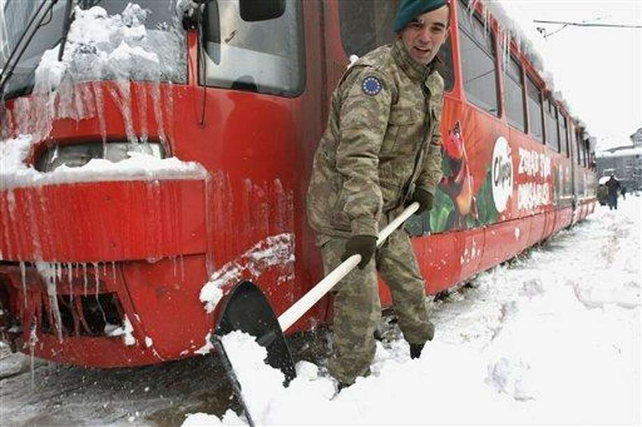 Turkish soldiers members of the European Union Force in Bosnia and Herzegovina, EUFOR, shovel snow from the tracks around a frozen tram as they work to normalize public transport in Bosnian capital of Sarajevo Sunday. Bosnia's government declared a state of emergency in its capital Saturday after Sarajevo was paralyzed by snow. Associated Press Photo: AP / AP