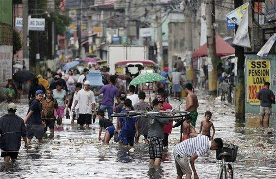 Filipinos wade through garbage-laden floodwaters at Navotas city, north of Manila, Philippines on Wednesday. Fierce winds and heavy rains from the slow-moving Typhoon Saola battered the country, displacing 154,000 people. Associated Press Photo: AP / AP
