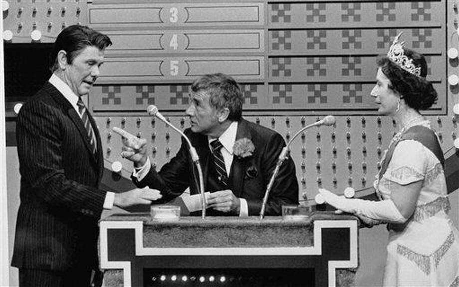 "In this Nov. 5, 1982 file photo provided by NBC-TV, ""Family Feud"" host Richard Dawson, center, gives President Reagan, played by ""Tonight Show"" host Johnny Carson, a chance at the big money as Queen Elizabeth (Rose Carr) readies herself at the buzzer during ""International Family Feud"" sketch on the show in Burbank, Calif. The ""feud"" pitted the Reagans against the Windsor family. Associated Press Photo: AP / AP1982"