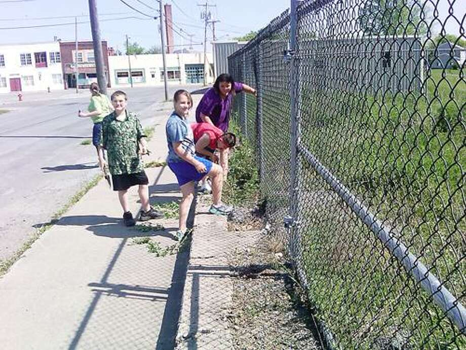 Photo Courtesy KIDS CLUB Members of Kids Club help clean up the Oneida Commons.