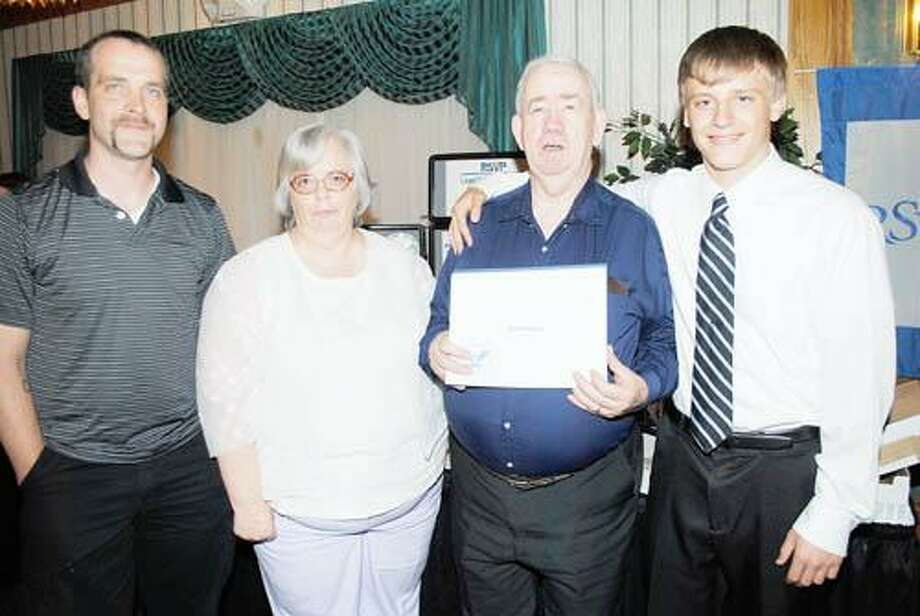 Photo Courtesy MADISON COUNTY RSVP Harold Mellen receives his award seen with his family. From left, Henry Farr, Carrie Mellen, Harold Mellen and Tanner Farr.